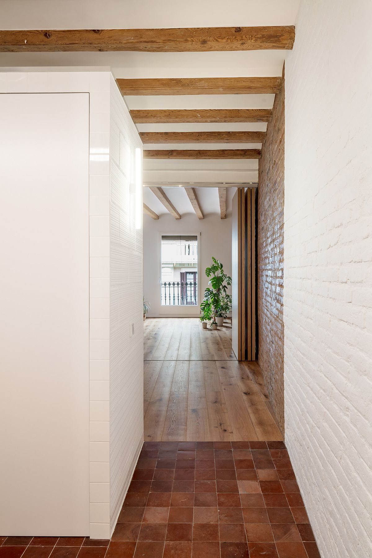Painted brick walls and exposed ceilings beams give the apartment a traditional look