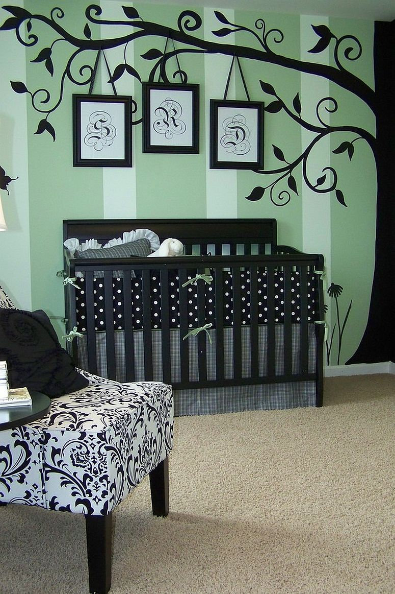 Painted tree wall mural accentuates stripes on the wall in the nursery