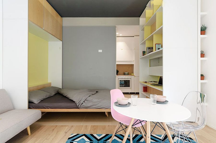 Pastel filled living room of micro apartment comes with a Murphy bed niche as well