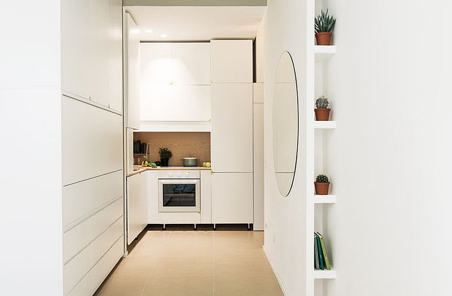 Sliding doors hide the tiny corner kitchen inside this micro Milan apartment