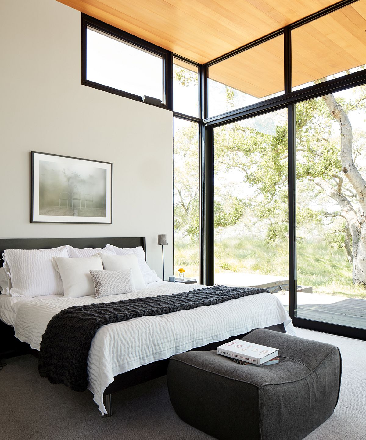 Sliding glass doors and windows connect the bedroom with the landscape