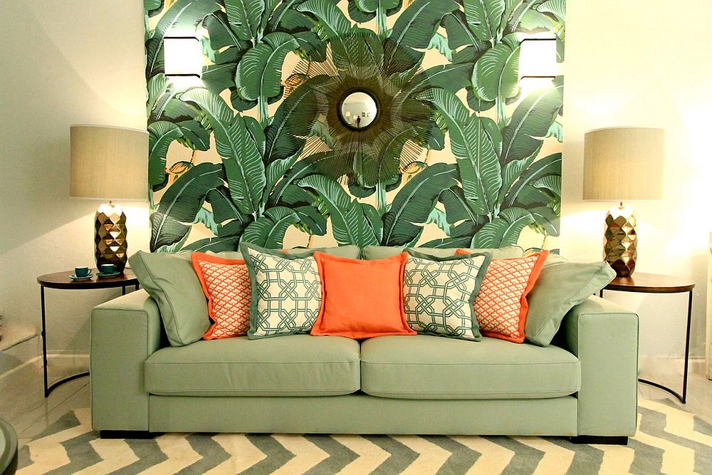 Sofa in light green with orange accent pillows matches the wallpaper beautifully