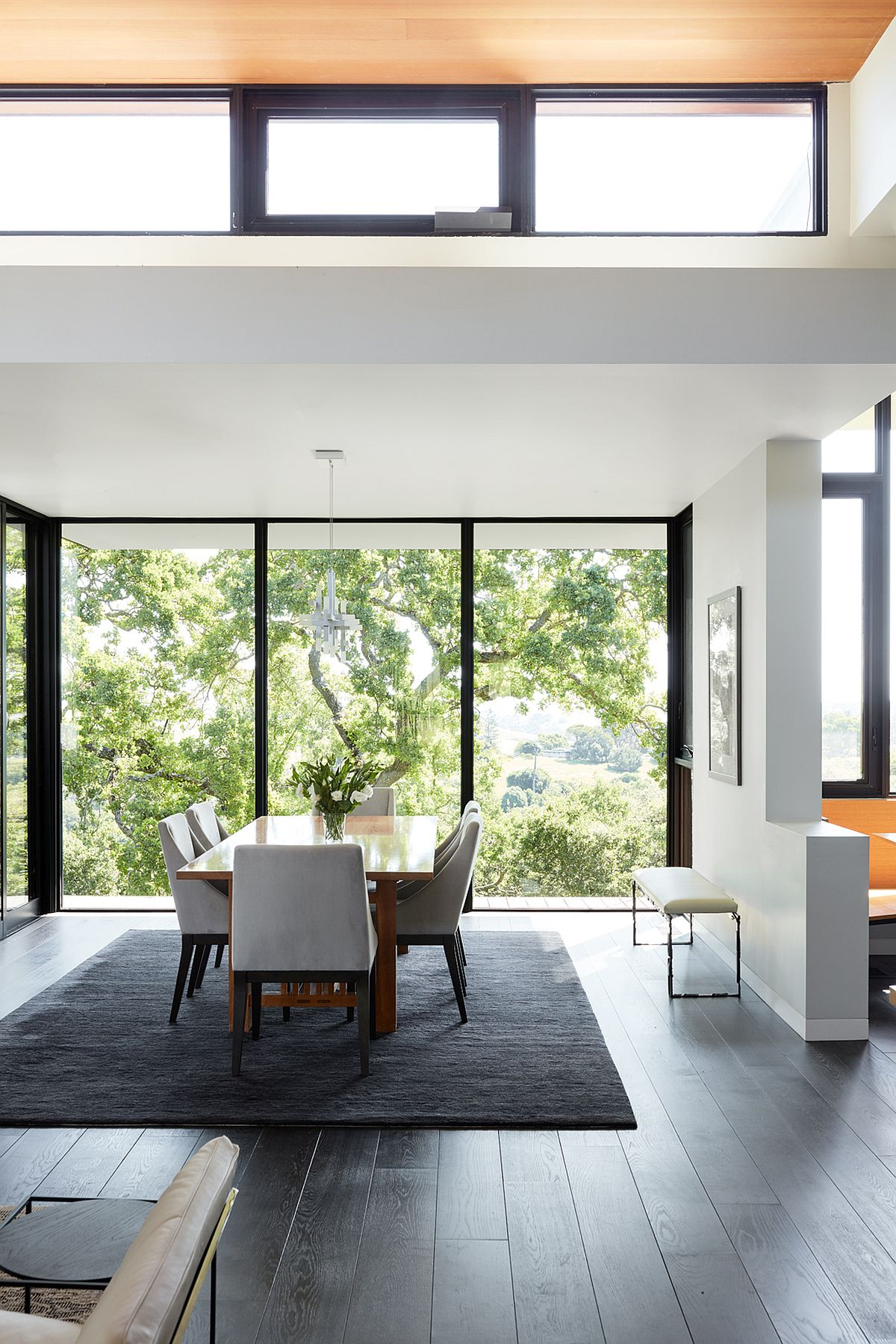 Spacious double-height dining area with a view of the woods outside