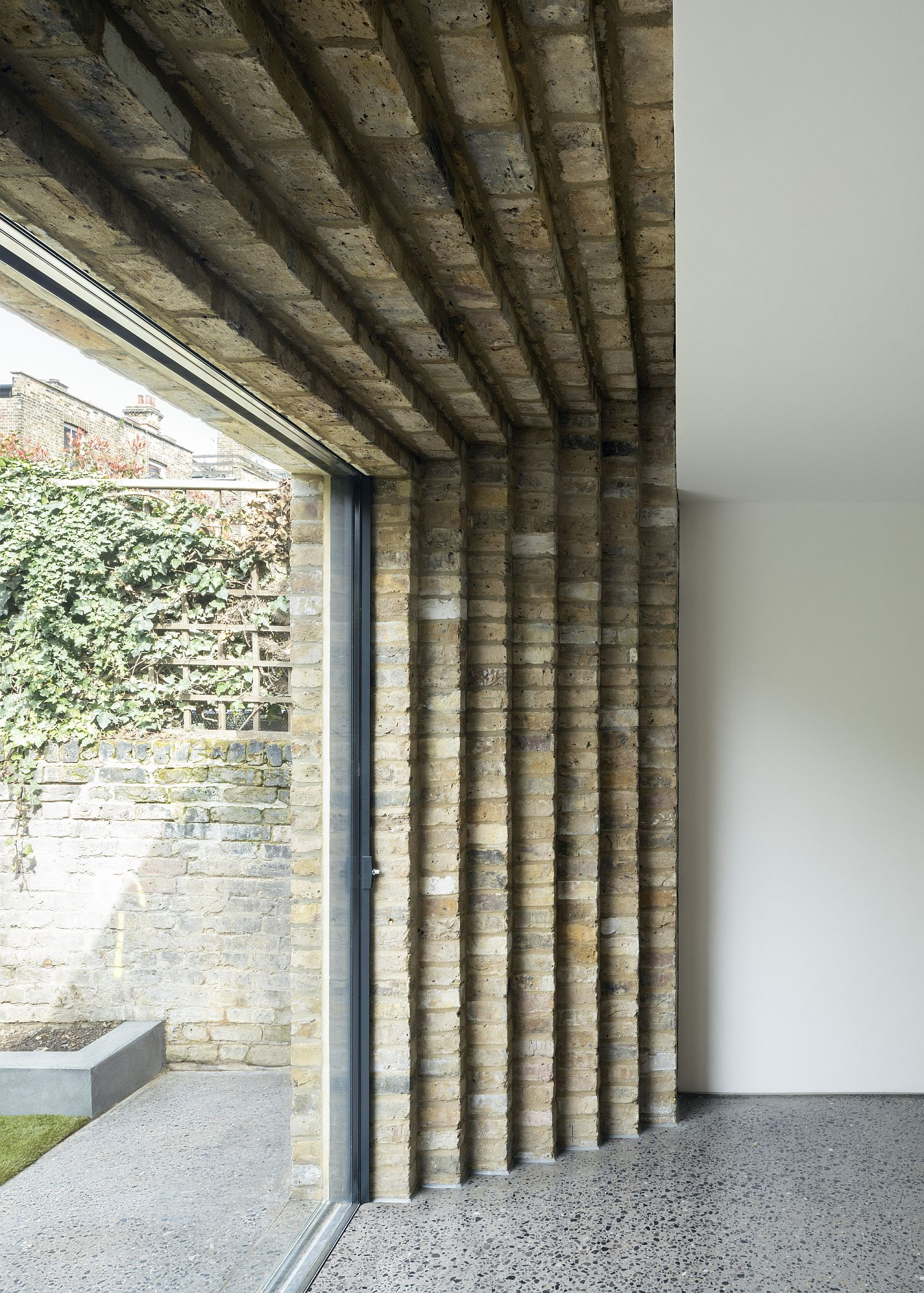 Step-styled brick wall extension of the London Residence