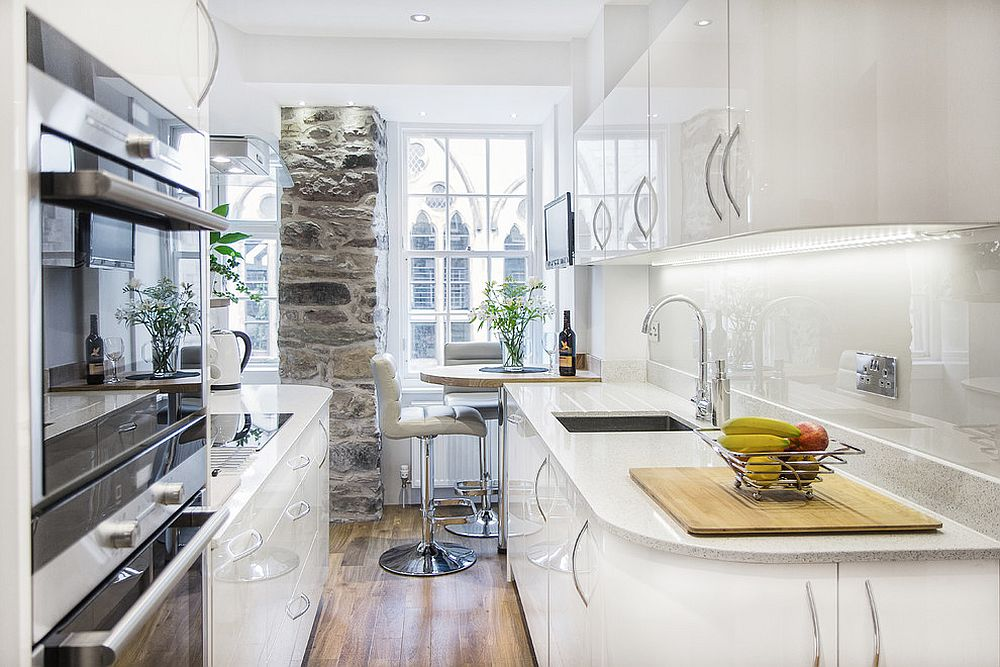Stone wall section adds character to the tiny kitchen in white