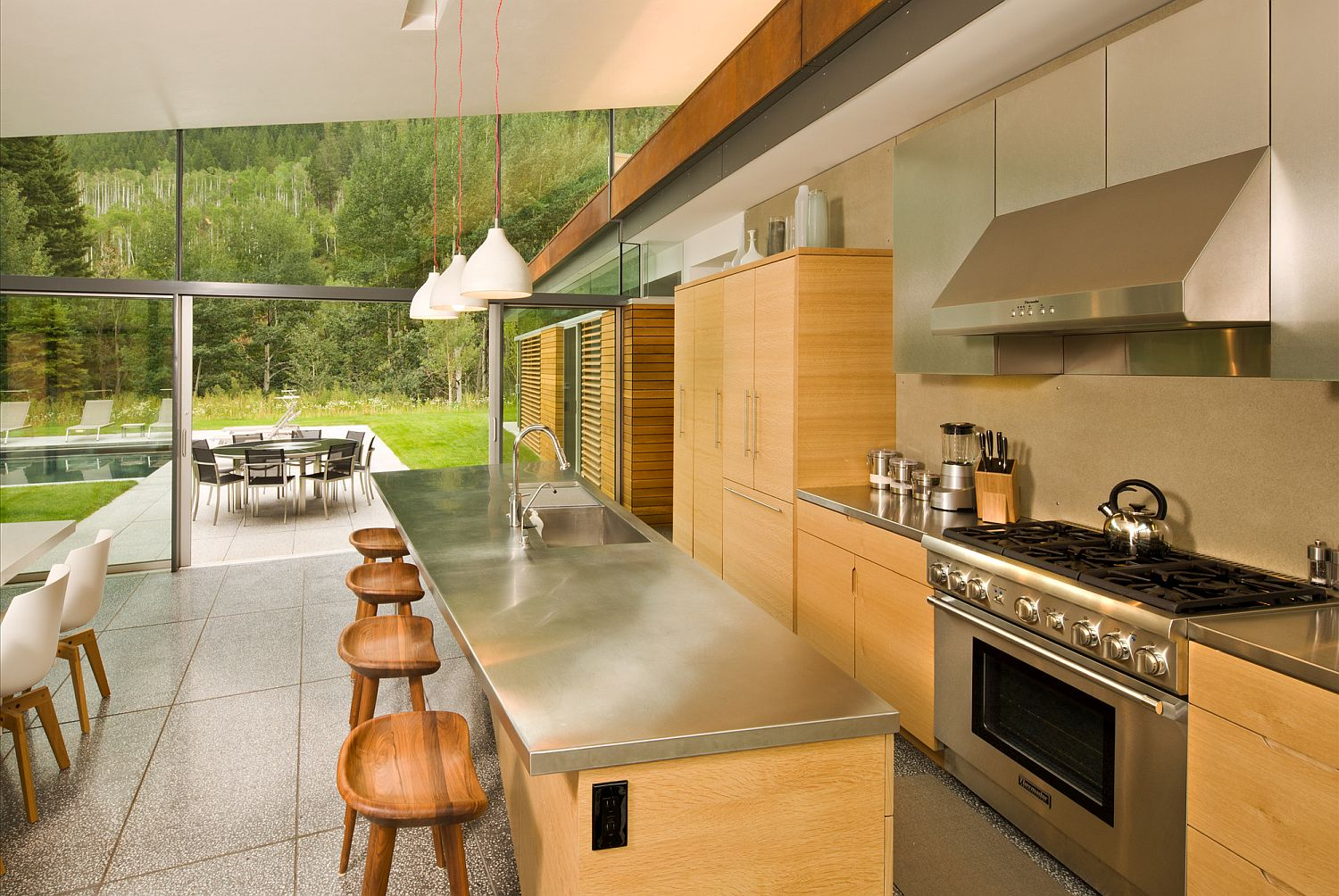 Wood and metal kitchen with a view of the pool outside