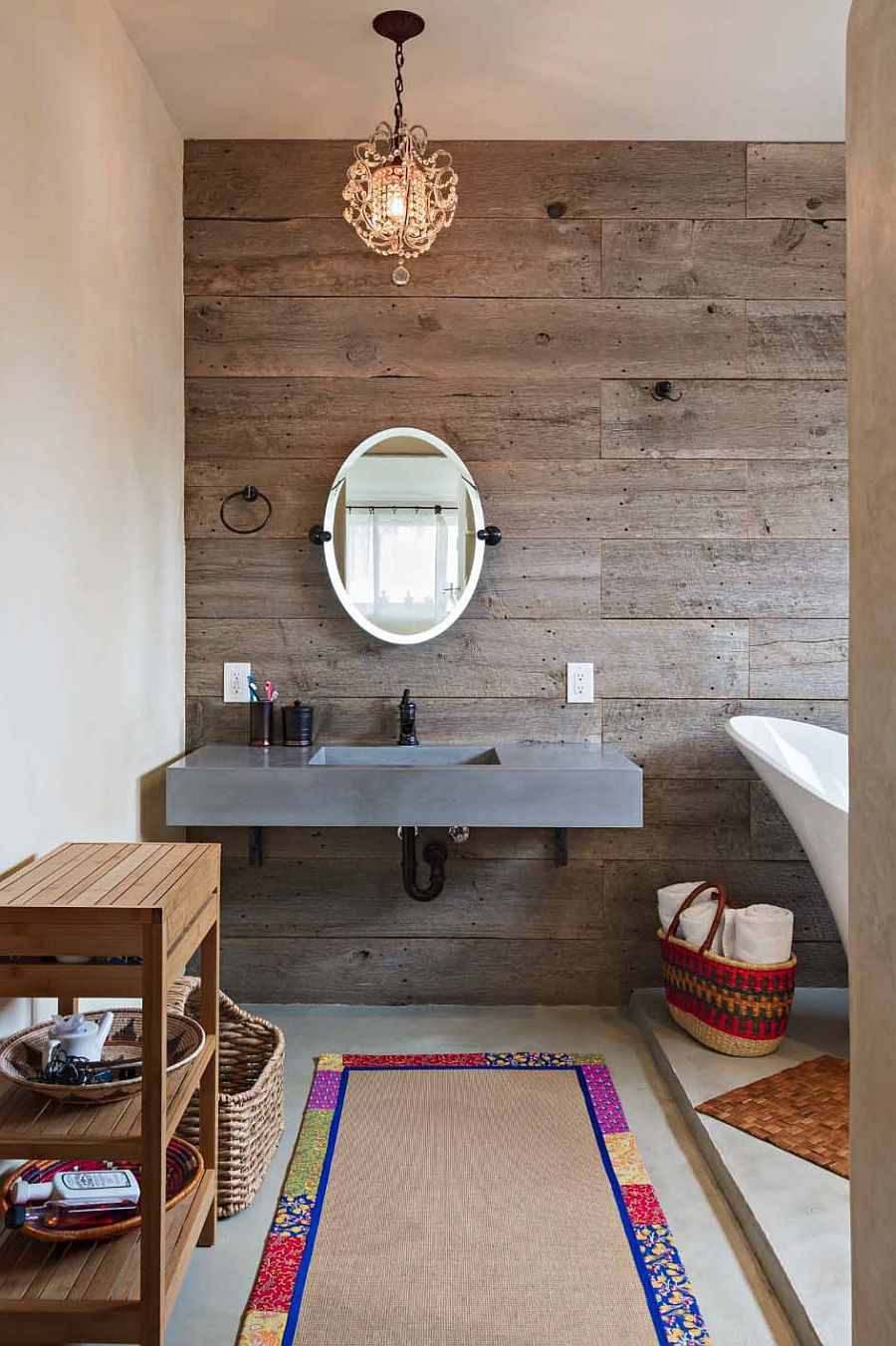 A concrete floating sink for the bathroom with wooden accent wall and traditional chandelier lighting