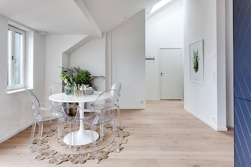 Acrylic chairs combined with round white table to create a lovely dining area