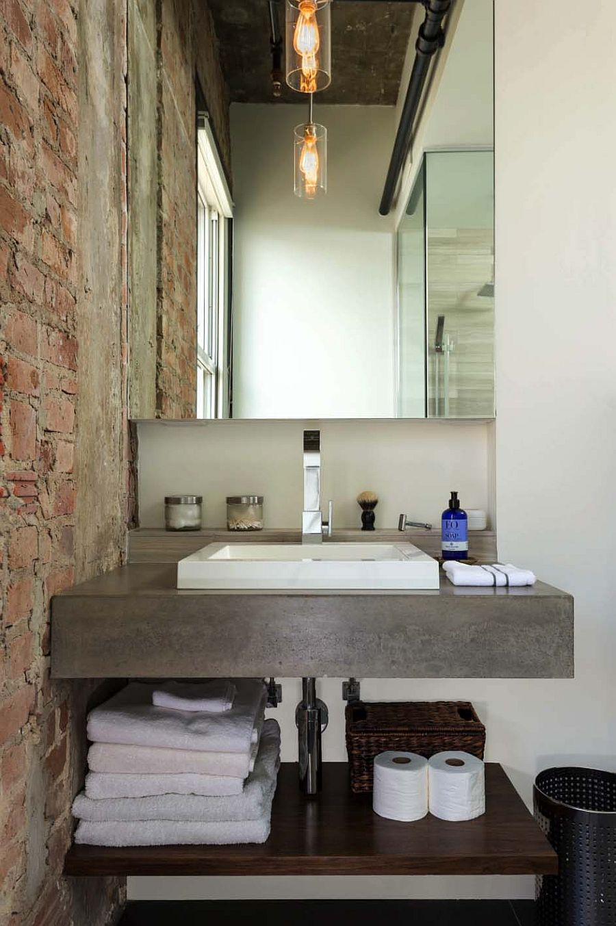 Concrete is combined with brick beautifully inside this modern industrial bathroom