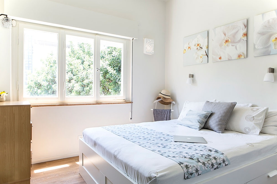 Contemporary-bedroom-in-white-with-wall-art-that-matches-the-color-scheme-of-the-room