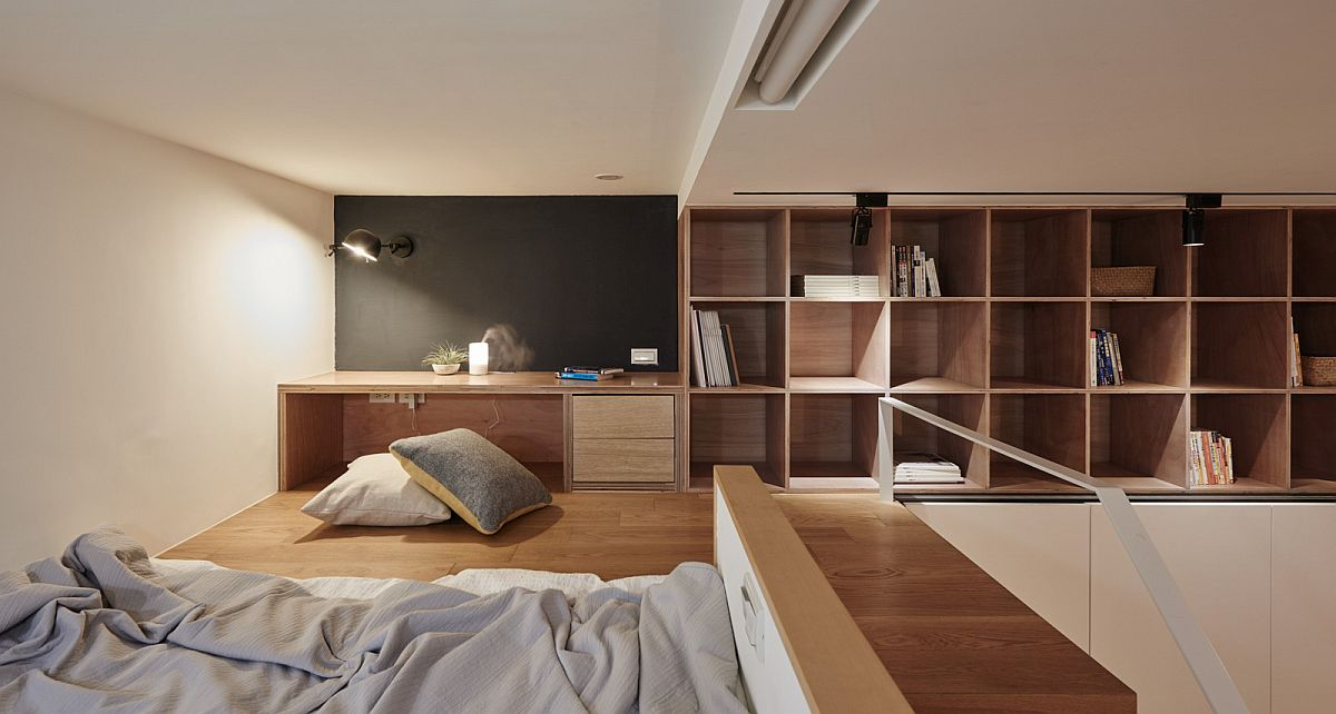Cozy-loft-level-bedroom-also-contains-a-tiny-workspace-and-ample-shelf-space-as-well