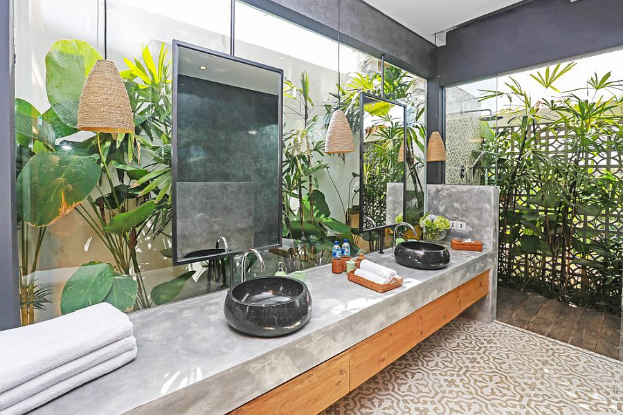 Gorgeous tropical bathroom with concrete and wood vanity and plenty of greenery