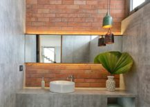 Industrial-bathroom-with-brick-accent-wall-is-draped-in-concrete-217x155