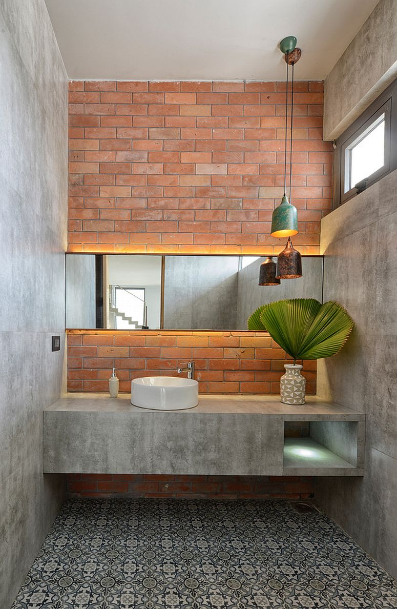Industrial bathroom with brick accent wall is draped in concrete