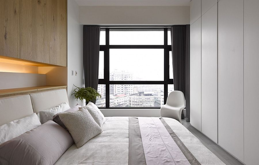 Minimal-apartment-bedroom-design-with-a-view-of-the-city-outside-the-window