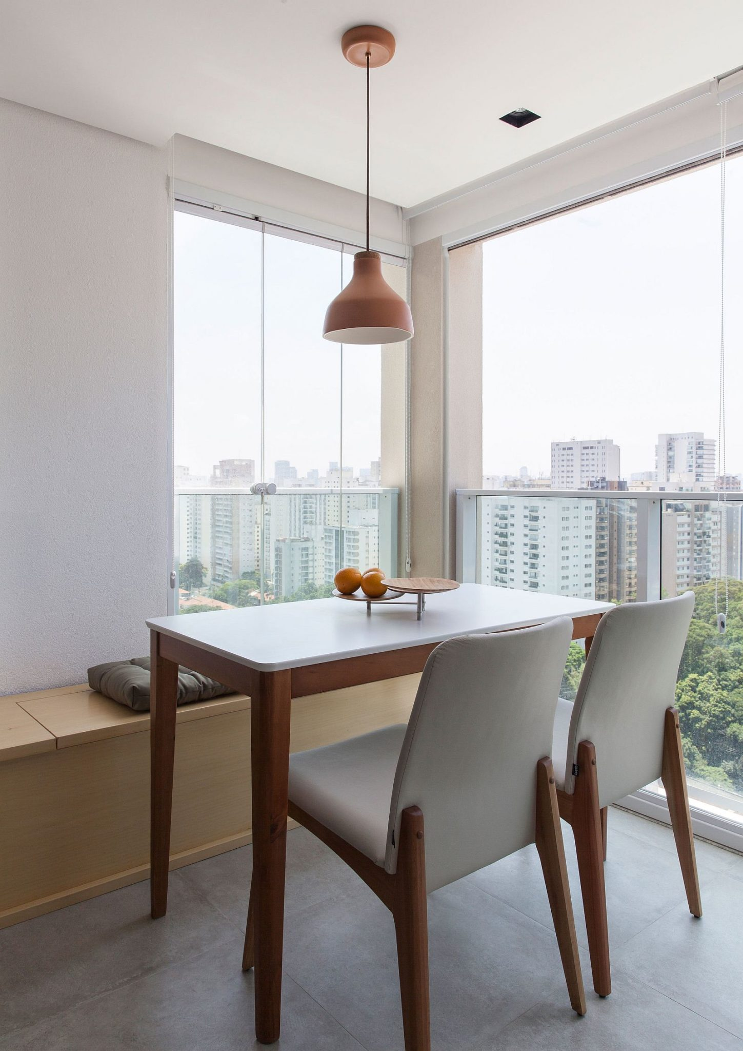 Polished little dining in the apartment corner with built-in storage and city views