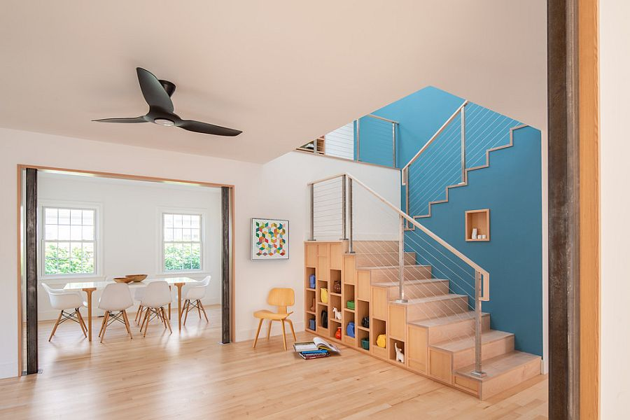 Staircase storage units help shape a lovely play area next to the dining room