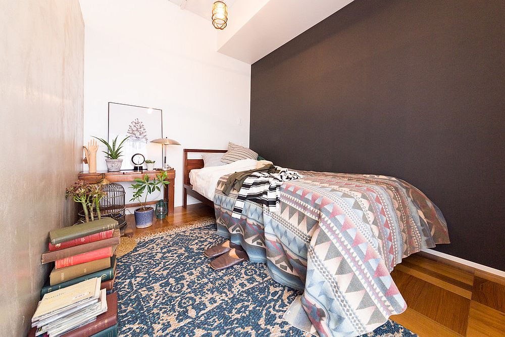 Tiny-modern-bedroom-of-Tokyo-apartment-with-stacks-of-book