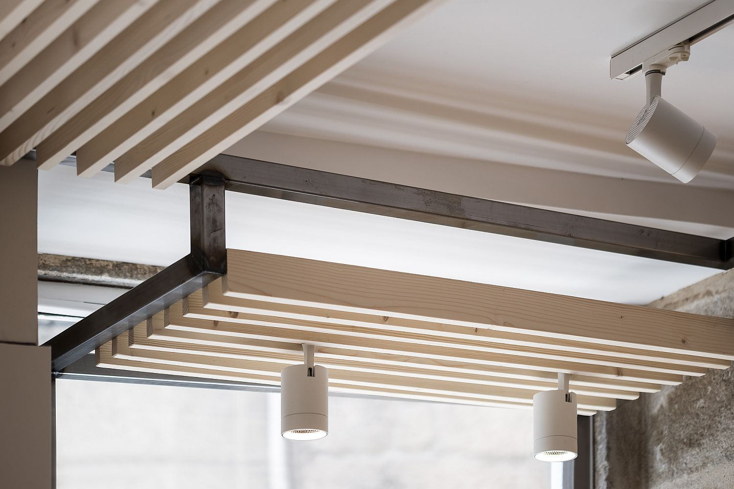 Wooden ceiling features and contemporary lighting of the restaurant