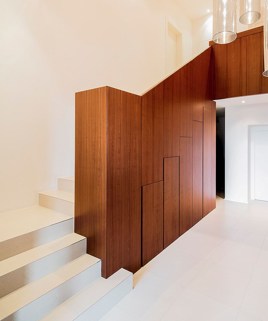 Wooden staircase wall morphs to offer smart and hidden storage underneath