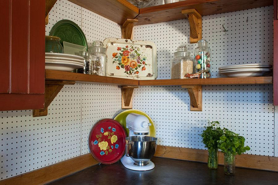 Corner of the rustic kitchen turned into storage space using pegboard on the walls