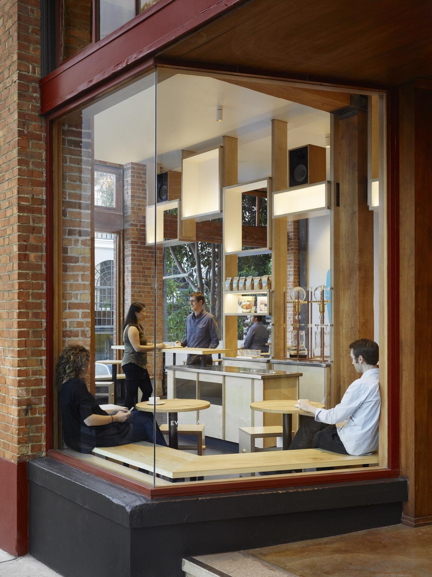 Corner-windows-and-elegant-birch-wood-seating-inside-Blue-Bottle-South-Park
