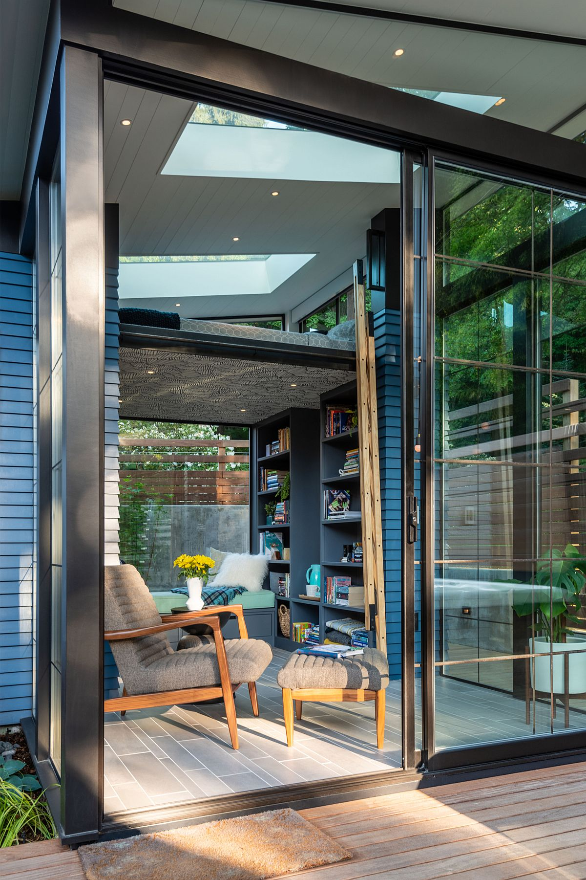 Glazed sliding glass doors connect the shed with the deck outside