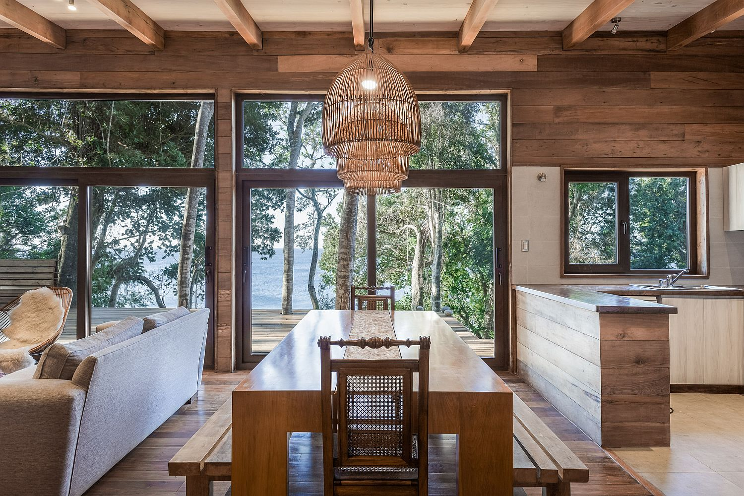 Kitchen-dining-are-and-living-room-of-lakeside-home-draped-in-wood