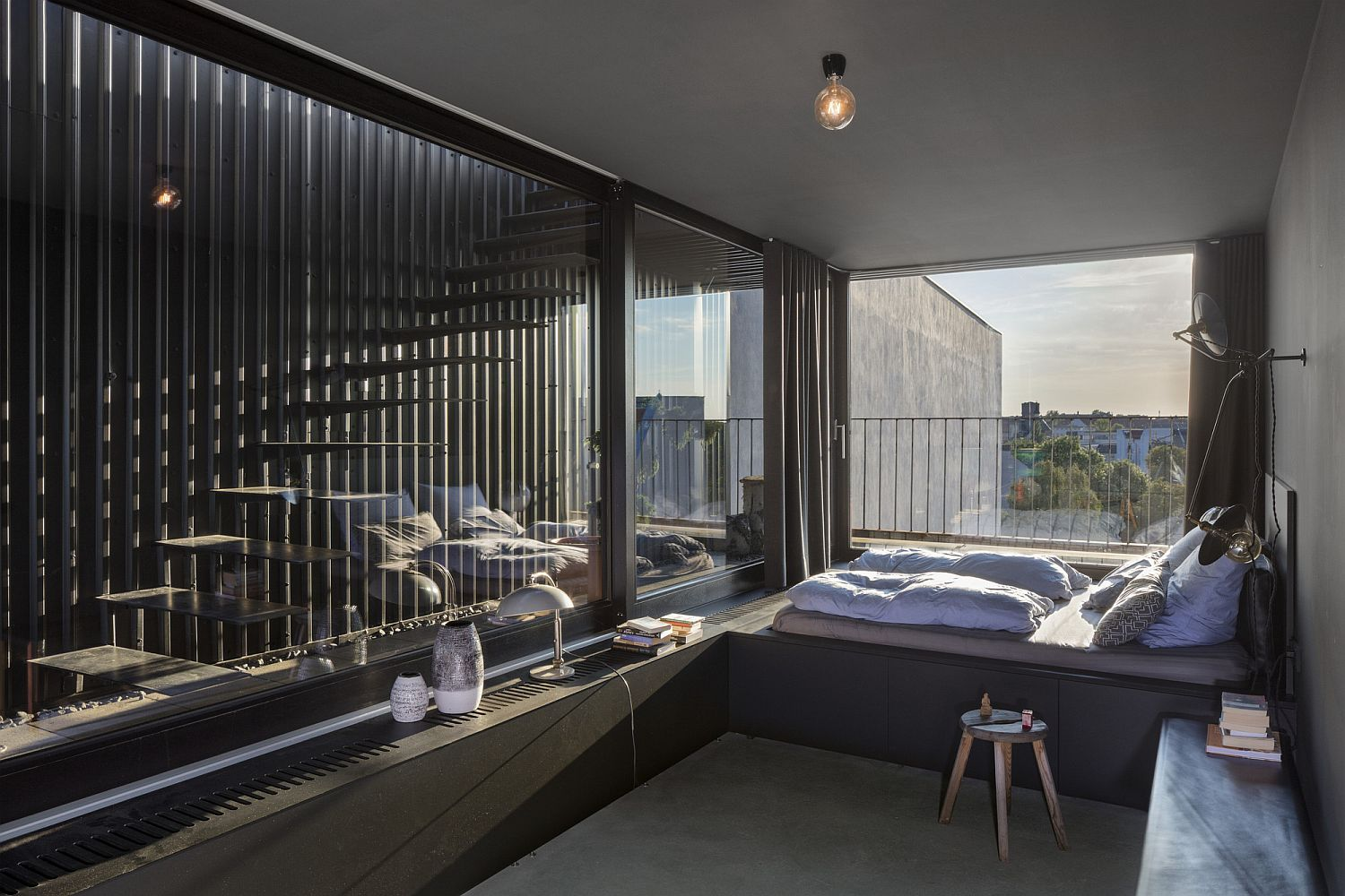 Light-filled-and-relaxing-penthouse-bedroom-with-stairway-next-to-it