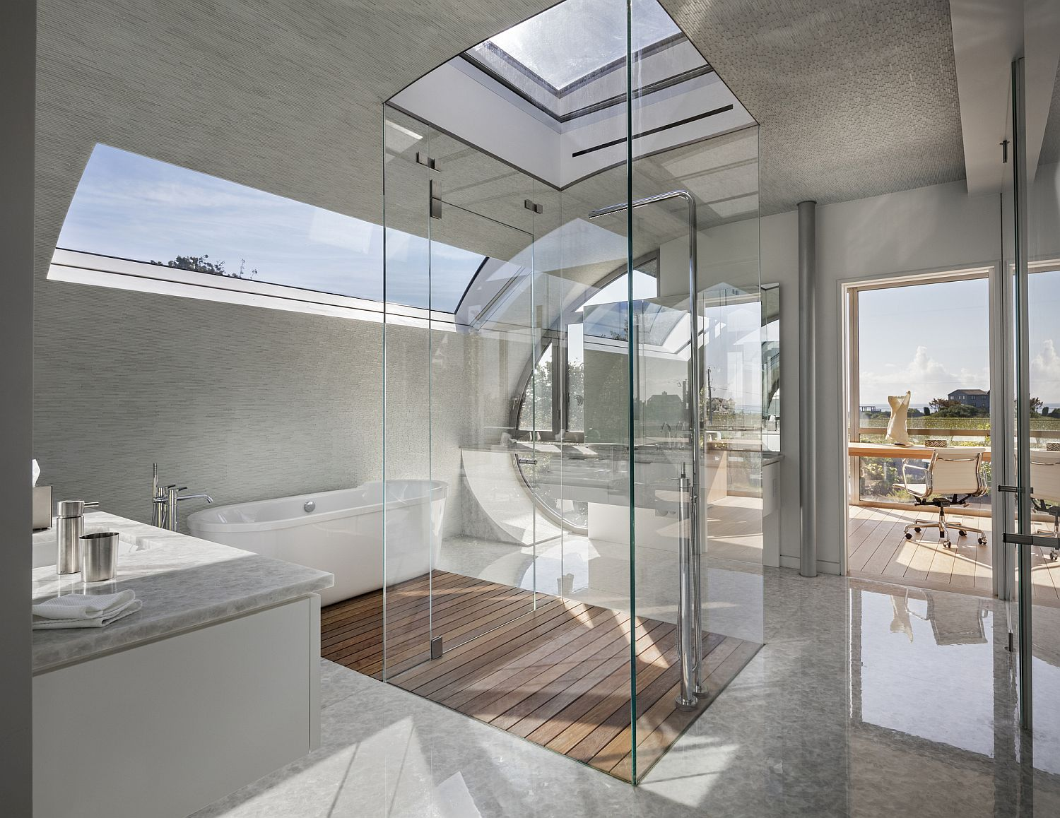 Lovely bathroom in white with an all-glass shower area and skylight