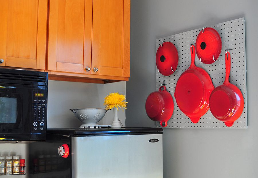 Pegboard with bright red pots and pans steals the show in this eclectic kitchen