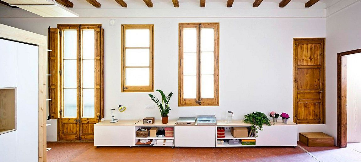 Refubished living space of Barcelona apartment with a smart, low-slung bookshelf