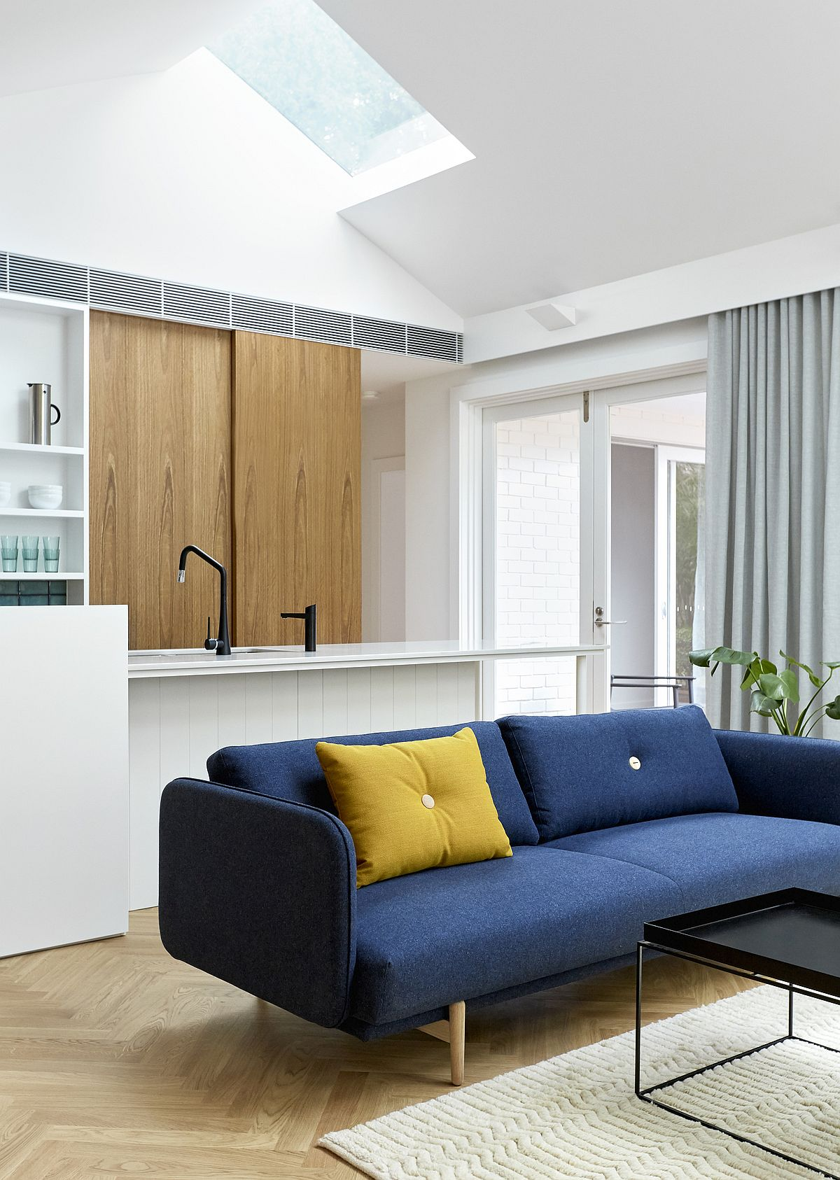 Scanidinavian-style-interior-with-blue-sectional-and-a-bright-yellow-accent-pillow