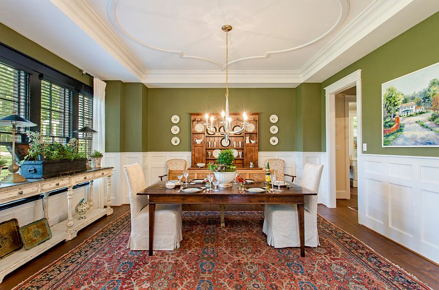 Transitional dining room in white and green with wooden dining table and shelving with distressed finish