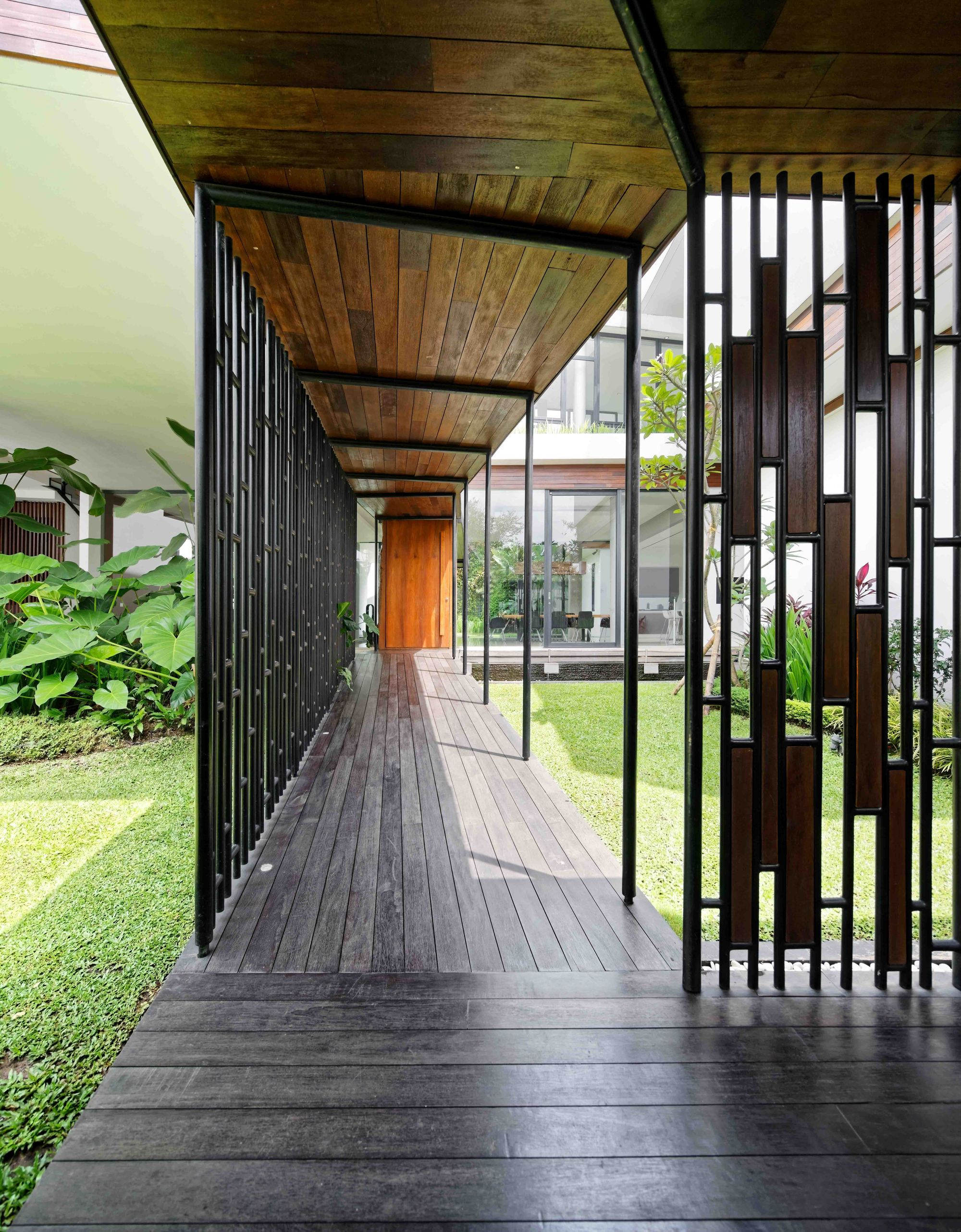 Wooden decks and corridors outside the house connect the different structures