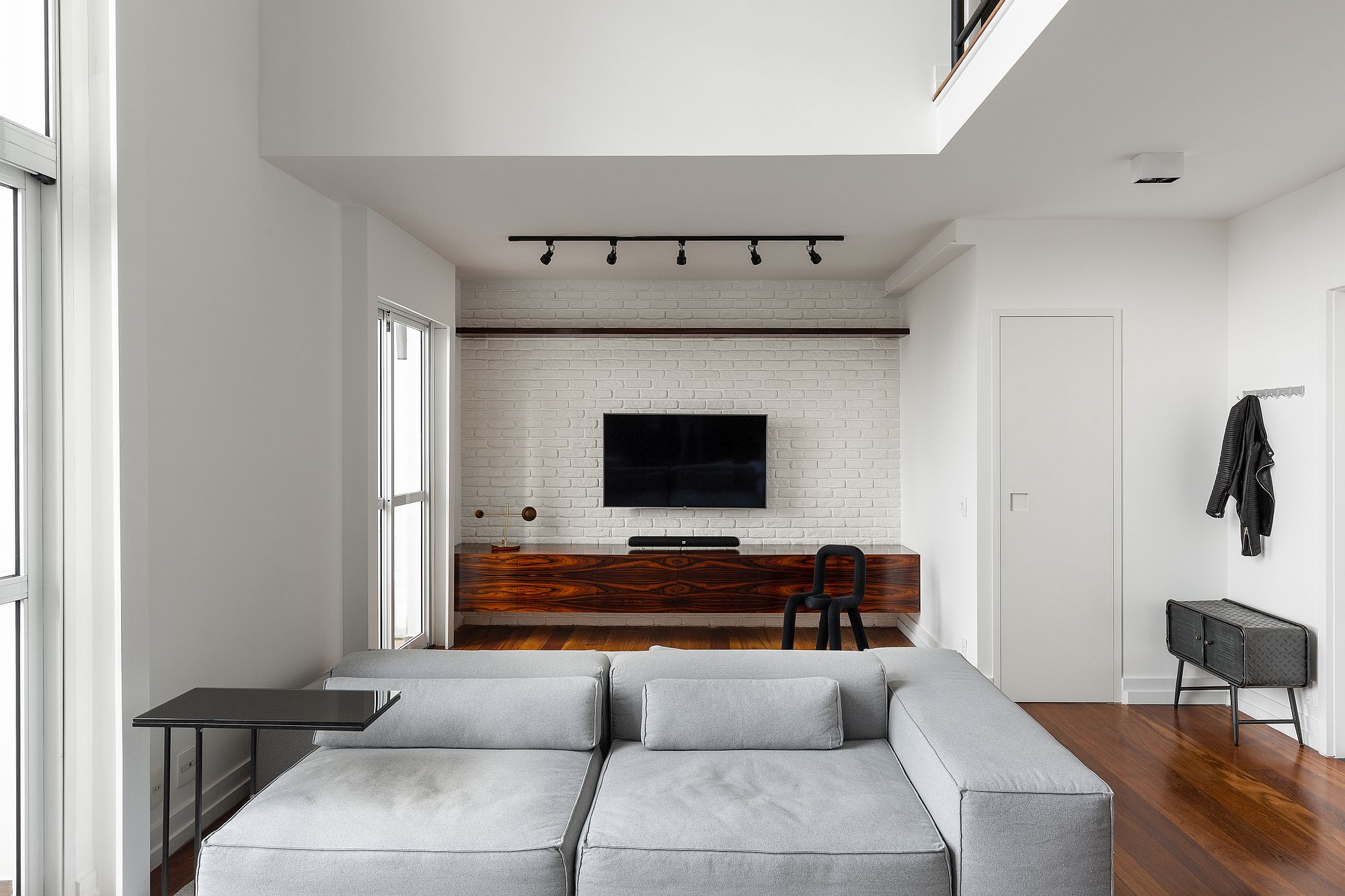 Wooden media unit stands out when placed before the whitewashed brick wall