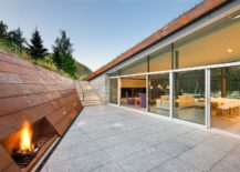 Corten-clad-wall-for-the-sunken-lounge-inside-the-mountain-home-with-green-roof-217x155