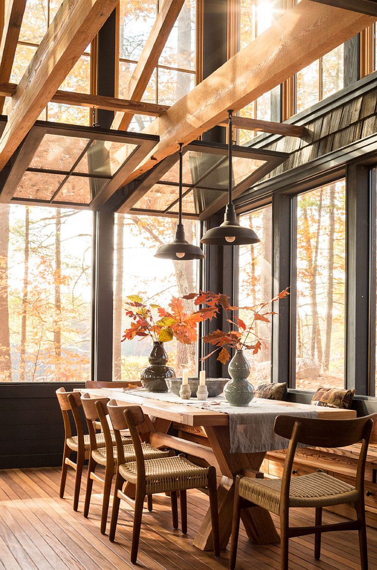 Nature outside adds fall beauty to this rustic dining space with glass walls