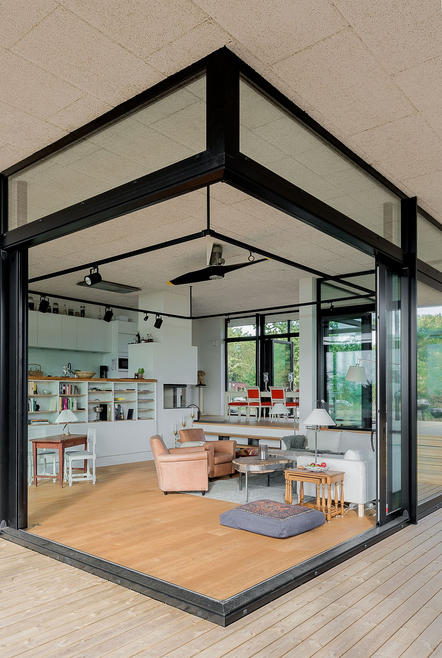 Sliding glass doors in the corner open the living room completely to the world outside