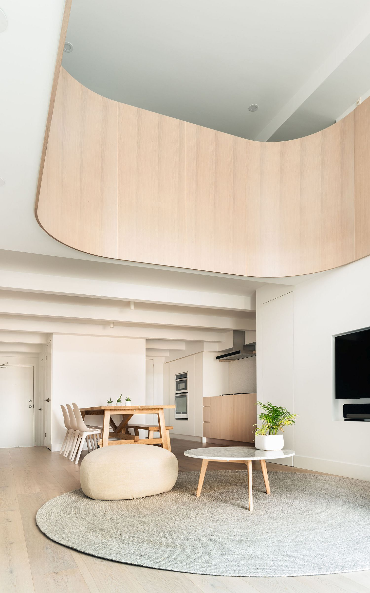 Curved wooden element lends softness to the minimal modern interior