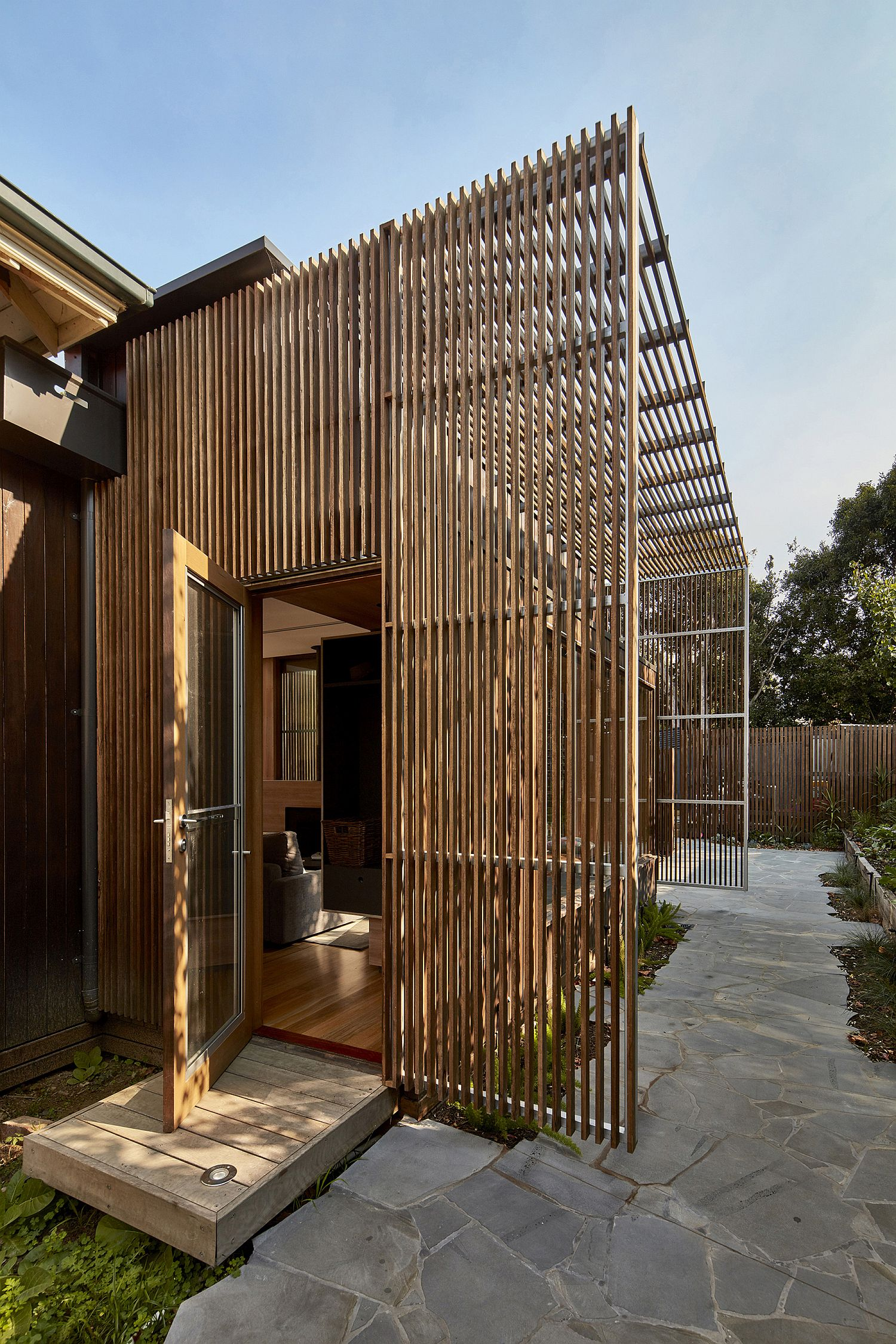 Custom timber screen creates a protected outdoor hangout while keeping out harsh sunlight