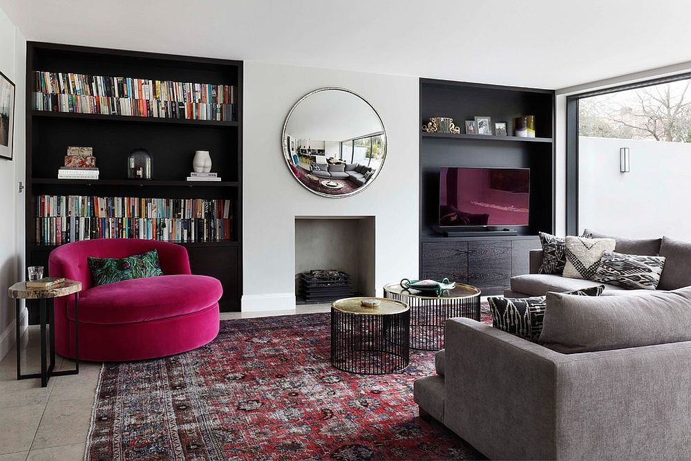 Dark shelving anchors the neutral room with pops of bright fuchsia