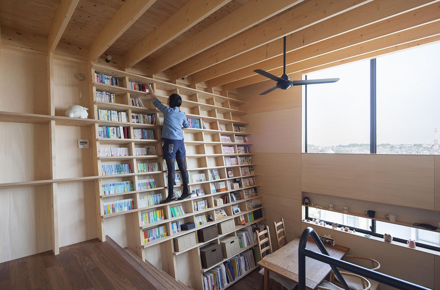 Double height living room with bookshelf wall is simply stunning