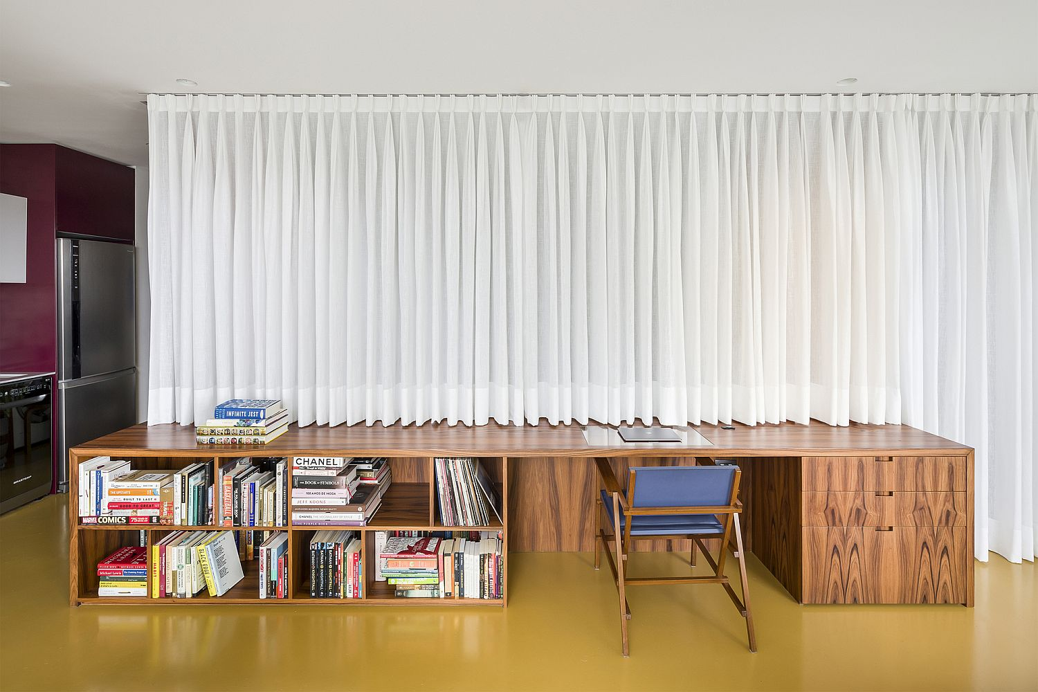 Drapes hide the bespoke wooden structure that contains the bedroom, bathroom and more