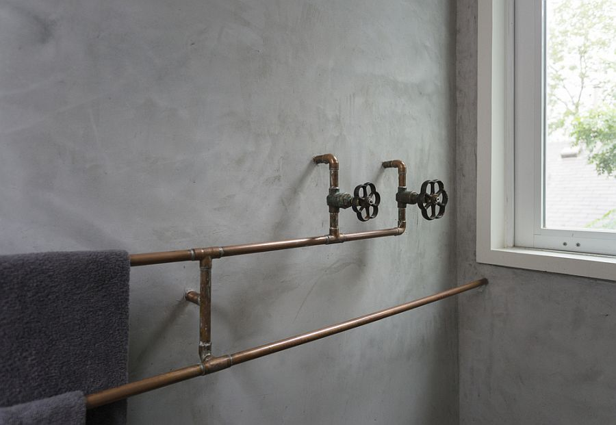 Exposed copper pipes in the bathroom with textural walls