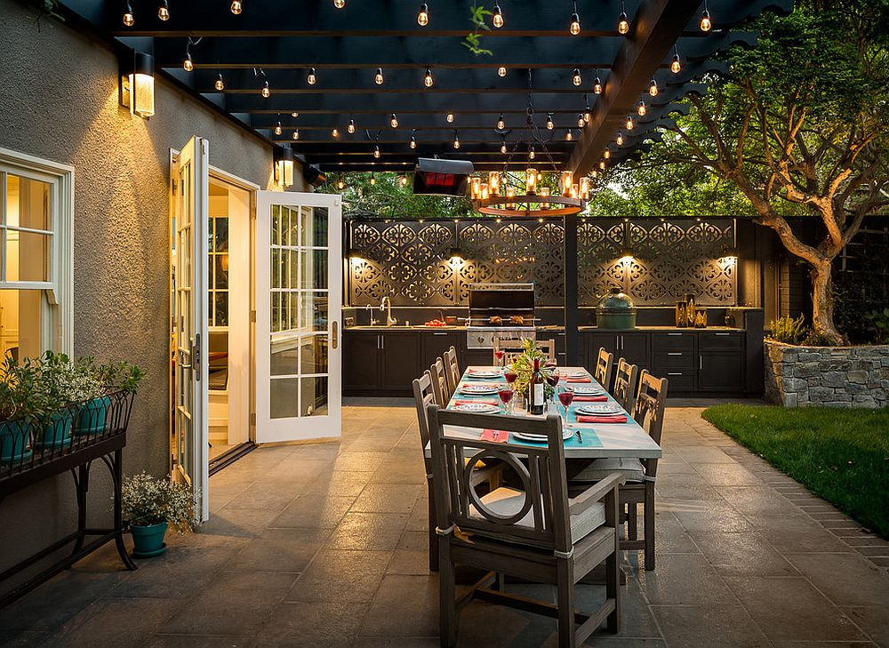 Gorgeous Edison bulbs illuminate the lovelly covered patio with outdoor kitchen and dining