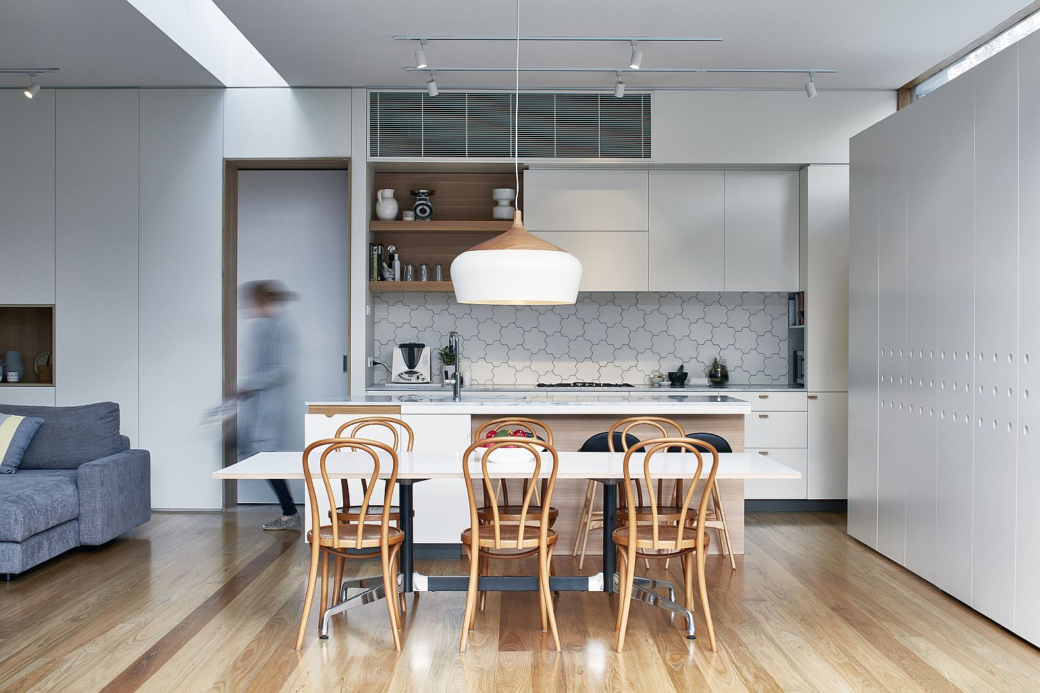 Modern kitchen with tiled backsplash and an oversized pendant above the counter