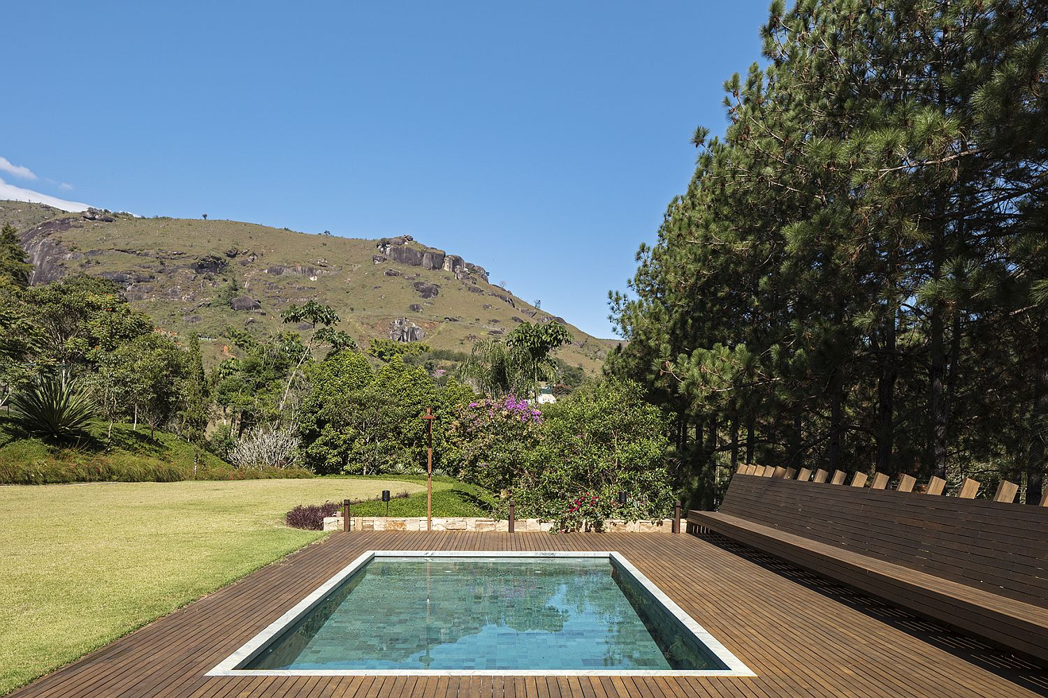 Pool with Hijau stone and wooden deck around it