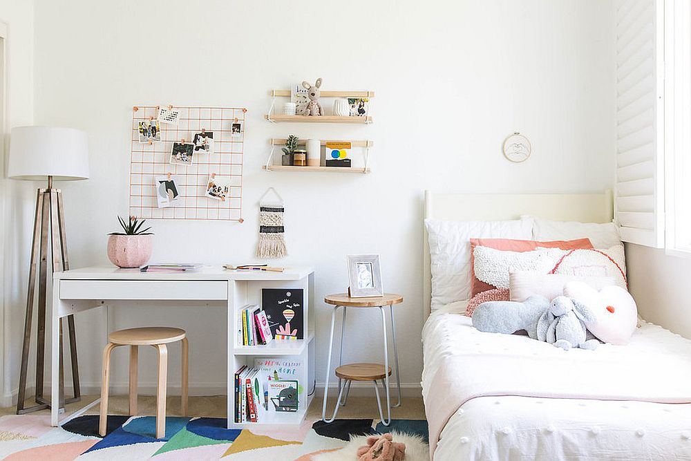 Scandinavian style kids' room with study space right next to the bed