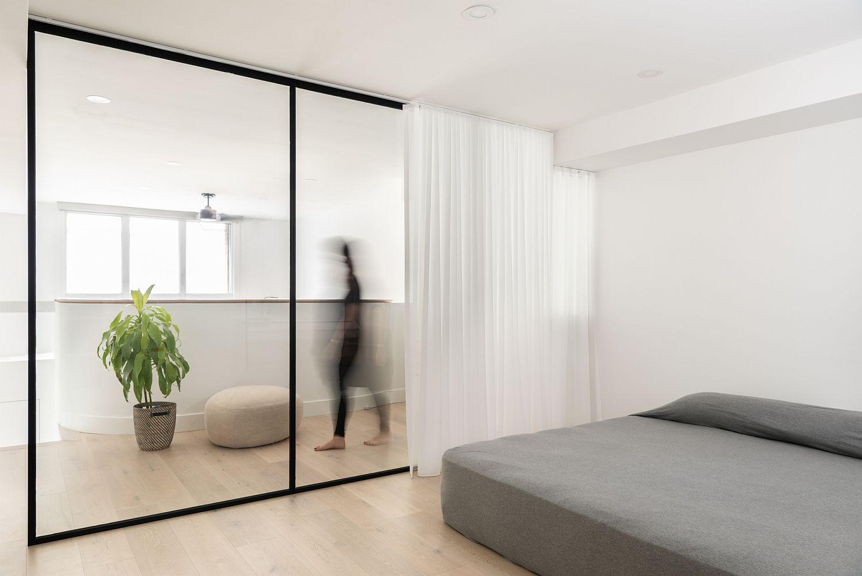 Sliding glass doors and white drapes for the upper level bedroom
